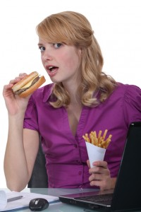 yay-9216562-woman-eat-burger-fries-at-desk