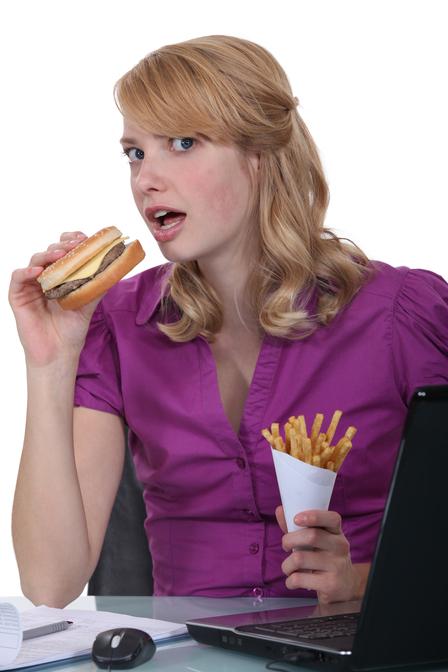 woman-eat-burger-fries-at-desk